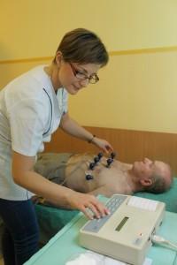 Pielęgniarka wykonuje EKG serca pacjentowi w Poradni Kardiologicznej tuż przed konsultacją u kardiologa